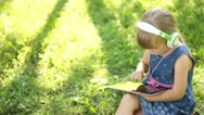 Little girl in headphones is online with a Tablet PC Stock Footage