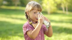 Pretty girl drinking milk and looking at camera. Milk mustache. - stock footage