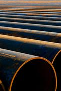 metal pipes laid out in a row for instalation - stock photo
