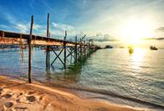 Wooden pier and boats in sunset lights Stock Photos