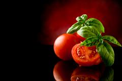 Sliced tomatoes with basil on glass table Stock Photos