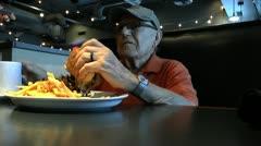 Elderly Man Eats Steak Sandwich Drinks Coffee At Diner Stock Footage