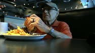 Stock Video Footage of Elderly Man Eats Steak Sandwich Drinks Coffee At Diner