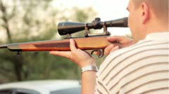 A man fires a rifle with a telescopic sight Stock Footage