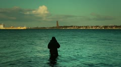 Fisherman at sunset with Laboe at horizon, Kiel, Germany Stock Footage