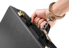 hand in a handcuff holding a suitcase - stock photo