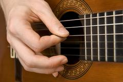 Guitar player's right hand picking the strings Stock Photos