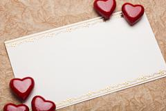 red hearts on card for text on paper background - stock photo