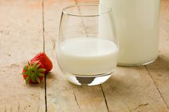 milk on wooden table with strawberry - stock photo