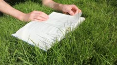 Reading book in grass Stock Footage