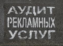 Advertising service audit as painted text on russian on asphalt, communicatio Stock Photos