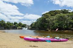 two kayaks in front of haruru falls, new zealand - stock photo