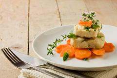 Cod on carrot bed with fresh oregano and basil Stock Photos