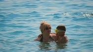 Vacationers mother with child boy luxuriate bathing in sea Stock Footage