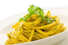 Stock Photo of pasta with saffron and arugula pesto isolated