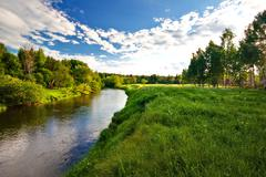 green field with small river - stock photo