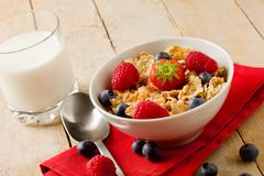 Corn flakes with berries on wooden table Stock Photos