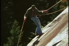 Mountain climbing school, guy lets out rope going down, Grand Teton National Stock Footage