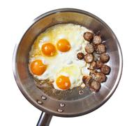 frying pan with sausage slices and eggs - stock photo