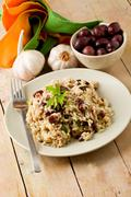 risotto with black olives on wooden table - stock photo