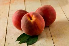 peach on wooden table - stock photo