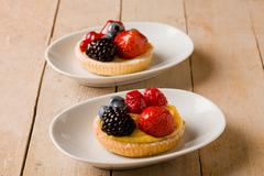 Pastry with berries on wooden table Stock Photos