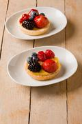 pastry with berries on wooden table - stock photo