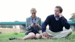 Young business people with cellphone relaxing outdoors, dolly shot HD - stock footage