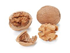 Walnut and a cracked walnuts  isolated on the white background Stock Photos