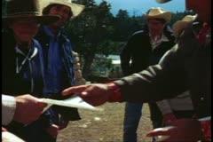 The Grand Canyon mule ride, medium shot, wrangler passes out diplomas Stock Footage