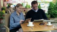 Stock Video Footage of Business people working with documents and tablet computer in cafe HD