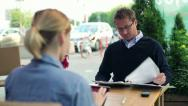 Business people working with documents and tablet computer in cafe HD Stock Footage