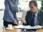 Angry businessman with tablet gets documents from employee in cafe NTSC Stock Footage