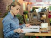 Businesswoman reading documents and drinking coffee in cafe NTSC Stock Footage