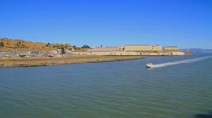 Boat passing in front of San Quentin State Prison in Marin County, California Stock Footage