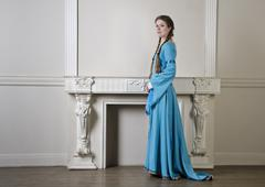Yound woman in historical dress near fireplace Stock Photos