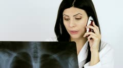Doctor talking on the phone with patient looking x ray Stock Footage