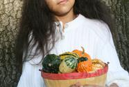 Stock Photo of Girl Holding Basket of Gourds