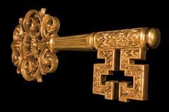 ornate gold key at an angle - stock photo