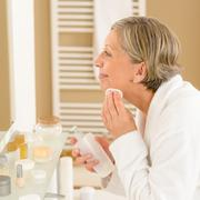 Senior woman apply face cleaning lotion Stock Photos