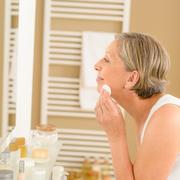 senior woman clean face with cotton pad - stock photo