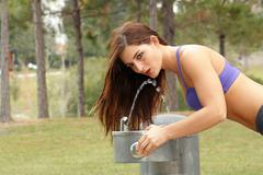Beautiful brunette athlete at a water fountain (1) Stock Photos