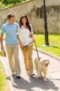 Young couple in love walking dog park Stock Photos