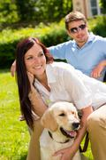 couple sitting with golden retriever in park - stock photo