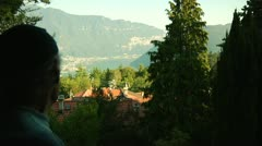 Elderly man looking out over lake in Switzerland Stock Footage