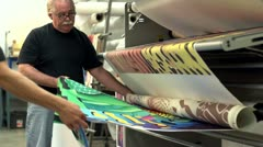 Printers pulling a finished textile out of a printer - stock footage