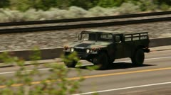 Military vehicles driving down the highway 4 Stock Footage