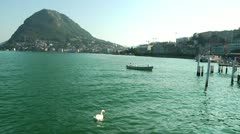 Swan and Fishing Boat on Picturesque Lake Lugano in Switzerland - stock footage