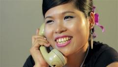 Retro young asian woman answering the phone - dolly shot Stock Footage