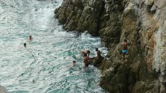 La Quebrada cliff diving site with several men climbing the rocky walls Stock Footage